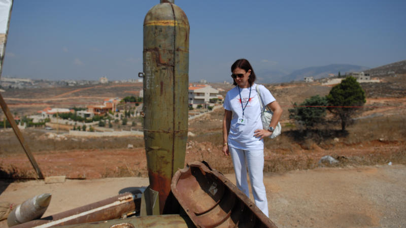 A campaigner stands by U.S. cluster munition remnants displayed at a field visit to Nabatiye during the convention's Second Meeting of States Parties (c) HRW, September 12, 2011