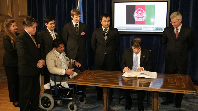 Afghanistan's Ambassador Jawed Ludin signs the Convention on Cluster Munitions in Oslo as cluster munition survivor Soraj Habib and other members of the Cluster Munition Coalition look on, December 3 (c) CCM, 2008